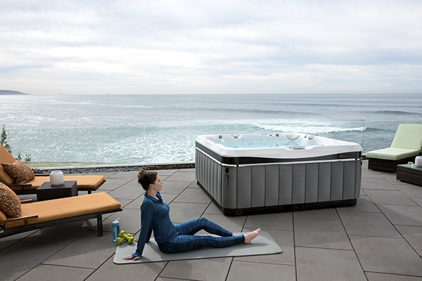 a woman performing yoga poses on a mat on her patio overlooking the ocean with a utopia tahitian jacuzzi