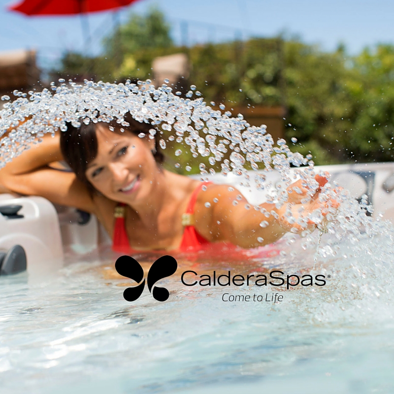 A lady stretches in her hot tub underneath the hot tub waterfall water feature