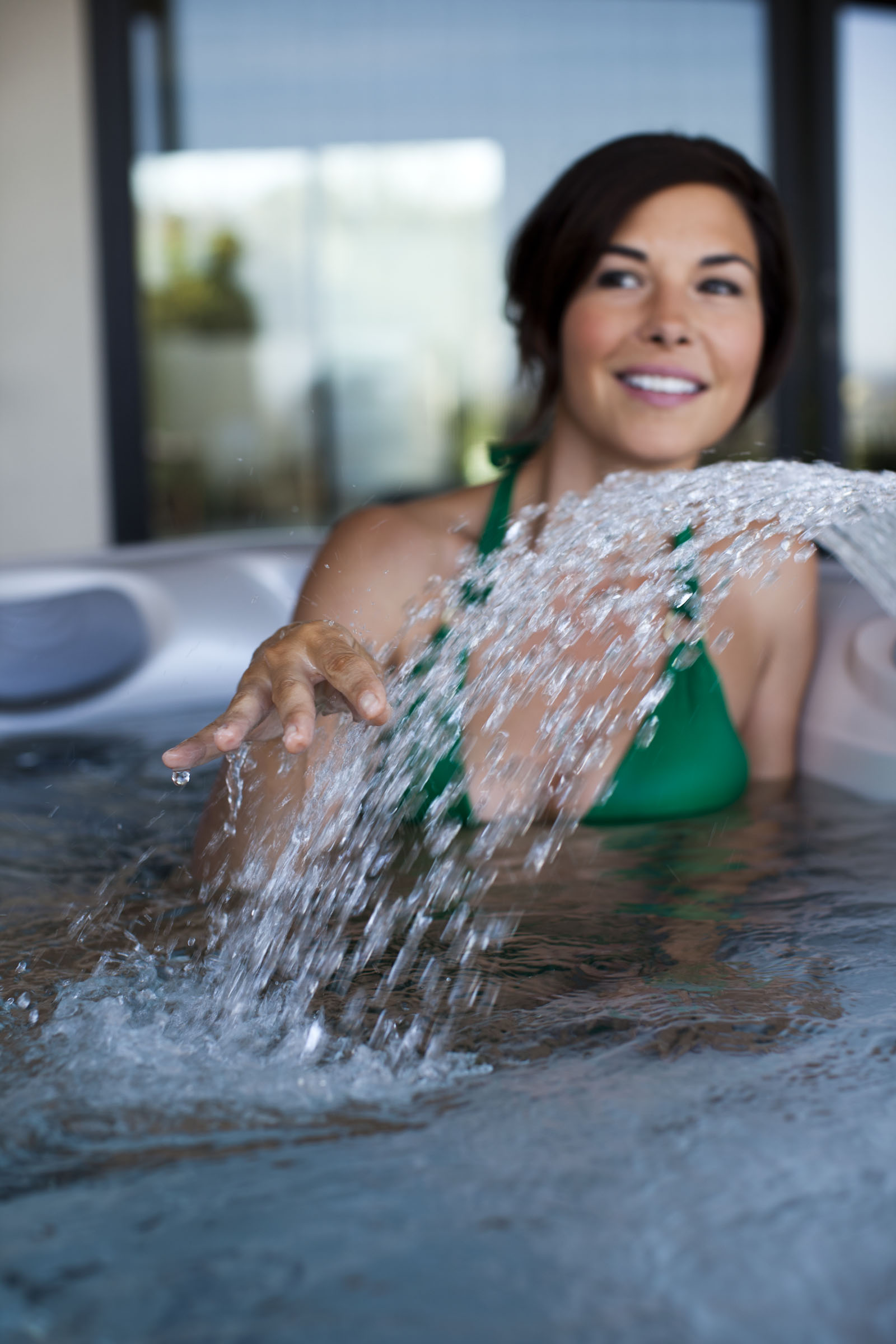 a woman enjoys the waterfall feature of her hot tub