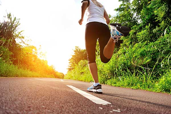 woman runs down a country road getting exercise in the early morning