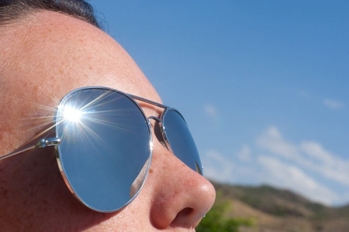 a close-up image of someone's face in the sun wearing sunglasses to warn about the dangers of summer sun exposure