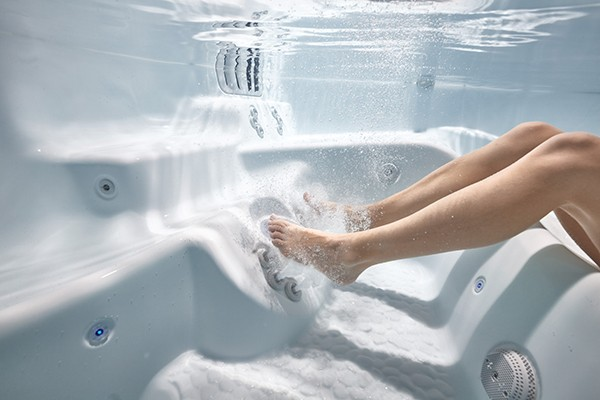 An underwater image of a ladies legs and feet getting a hot tub foot massage