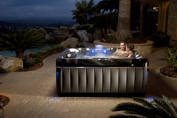 A couple relaxes in a Utopia Niagara spa on a beautiful star lit evening on a tropical styled patio
