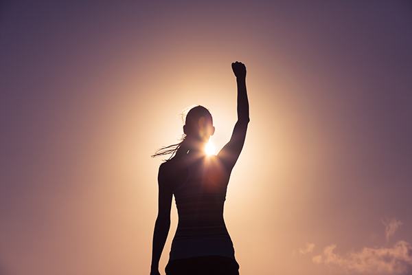a silhouetted lady stands triumphantly with her fist raised