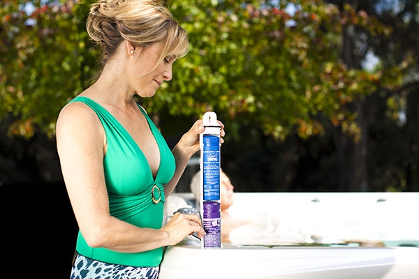 a woman easily changes her chemical cartridge to maintain her hot tub