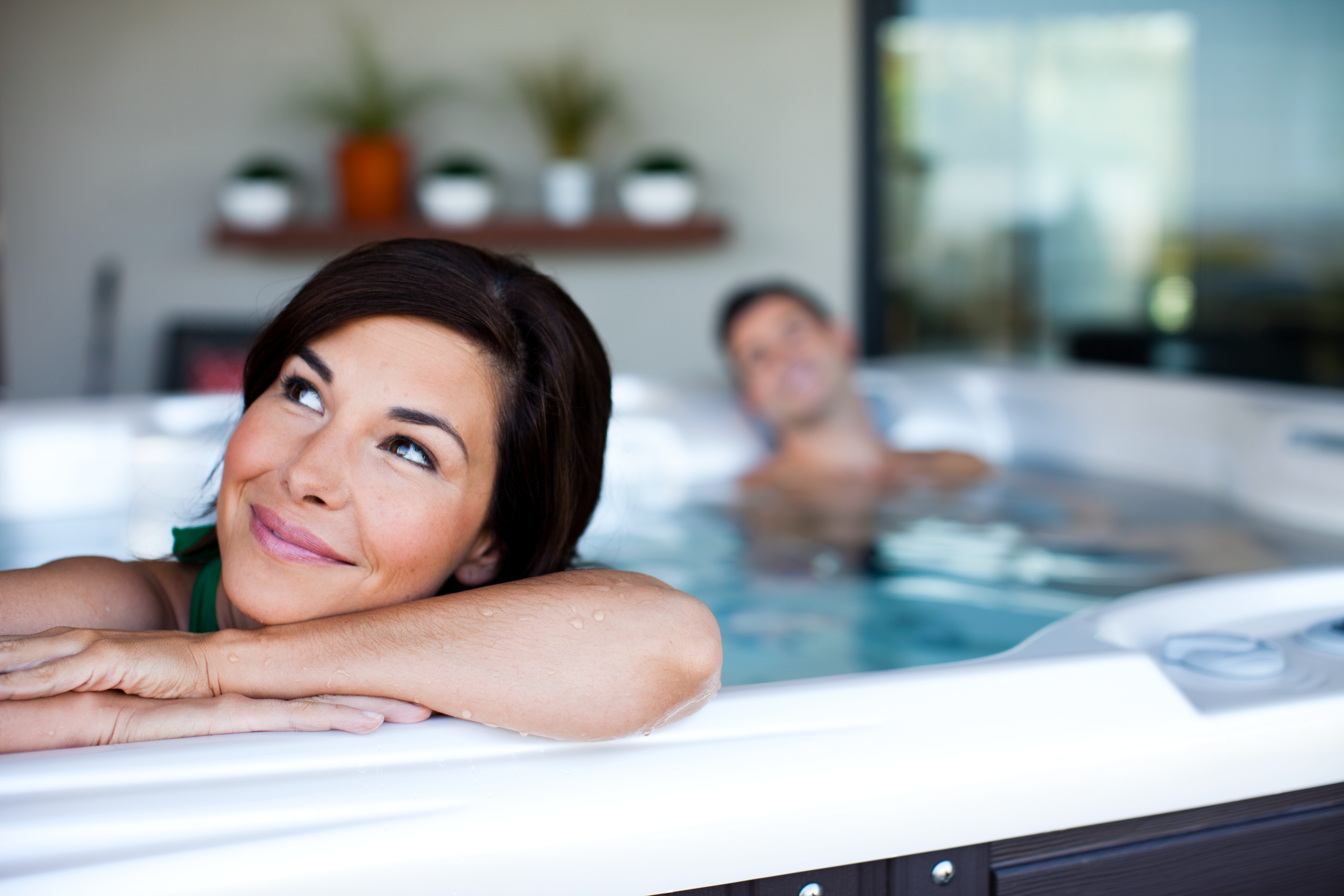 couple relaxes in a vacanza tarino hot tub with a pearl colored shell on a beautiful back yard patio
