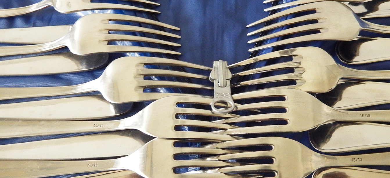 image of dinner forks on top of a zippered bag