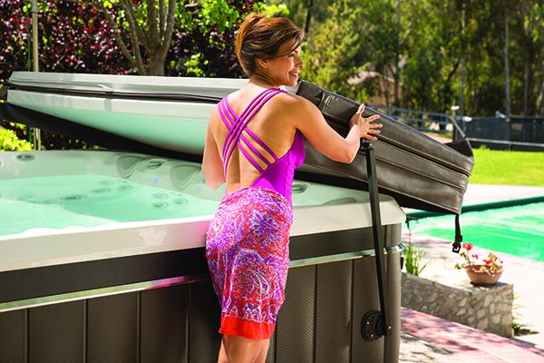 woman operates hot tub cover caldera hot tub reviews and benefits